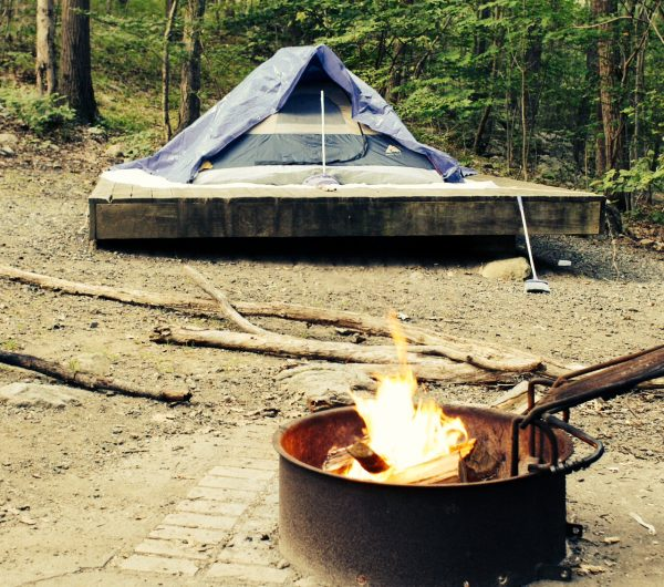 Blue tent on elevate platform with open campfire